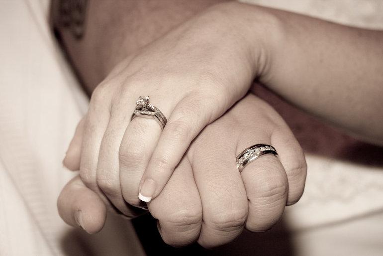 Egymásba fonódott kezek, jeggyűrűvel