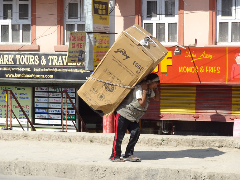 Nagy dobozt cipelő ember