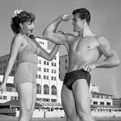 Egy nő elismerően tapogatja egy férfi izmait