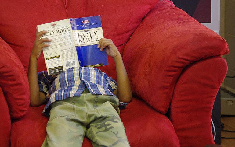 Egy ember kanapén fekve Bibliát olvas