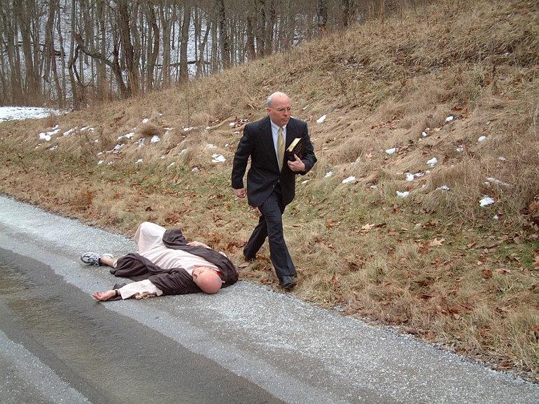 Egy fekvő ember mellett elhaladó férfi Bibliával a kezében