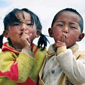Két gyerek szájuk elé tett kezekkel csendre int