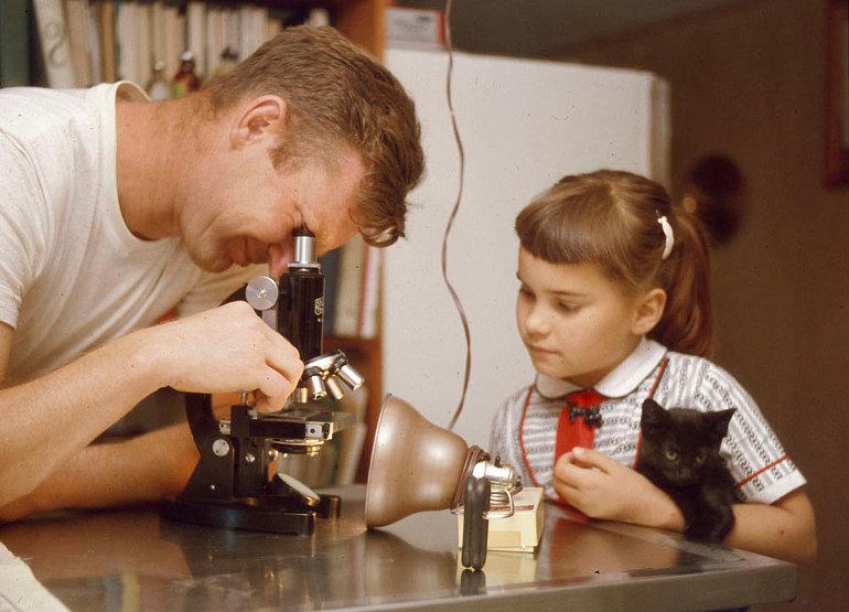 Egy férfi egy asztalon levő mikroszkópba néz