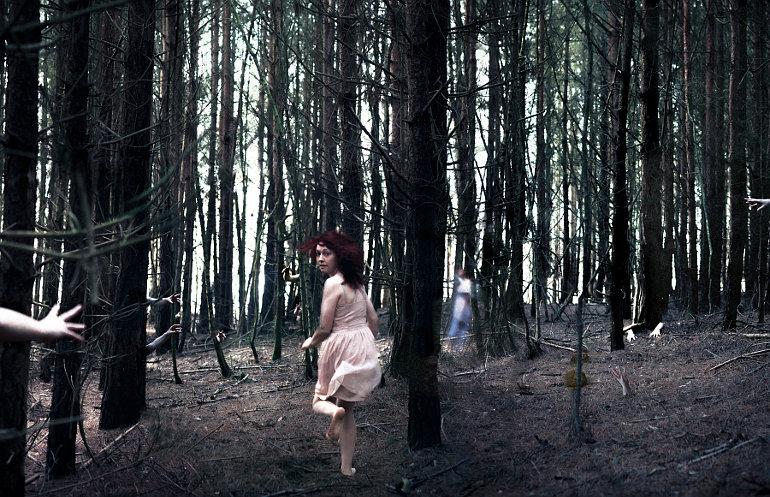 Menekülő nő egy erdő fái között