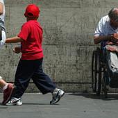 Anya gyermekével elhalad egy hajléktalan mellett