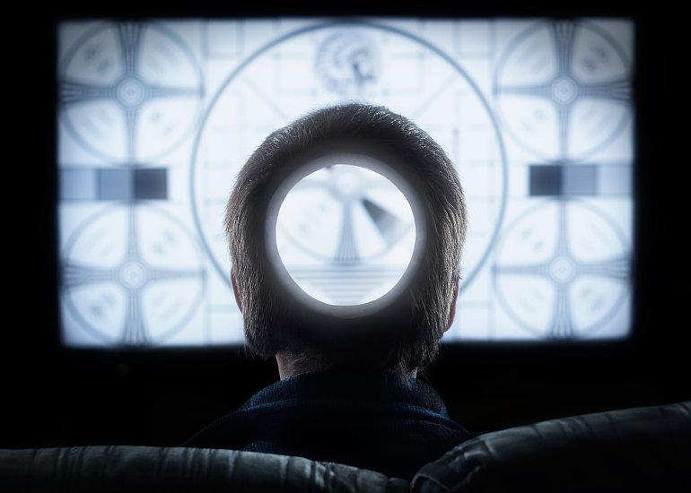 Egy ember ül a TV előtt, a fején egy hatalmas lyuk tátong