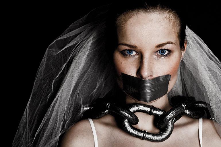 Menyasszony beragasztott szájjal, nyakán lánccal