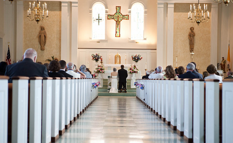 Vőlegény és menyasszony az oltár előtt térdel