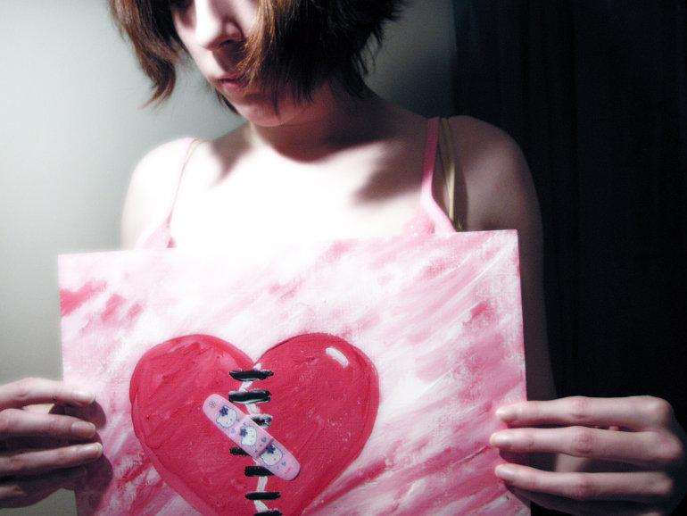 Lány, kezében törött szívet ábrázoló rajzzal