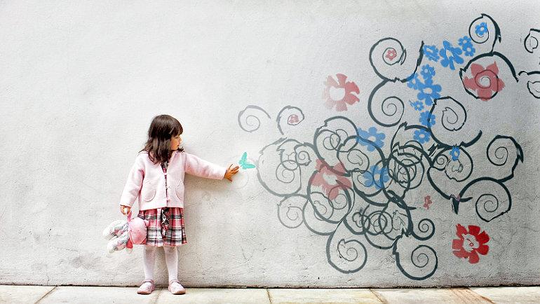 Kislány egy virágokkal díszített falnál