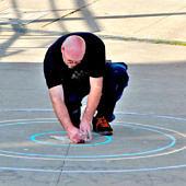 Egy férfi köröket rajzol az aszfaltra