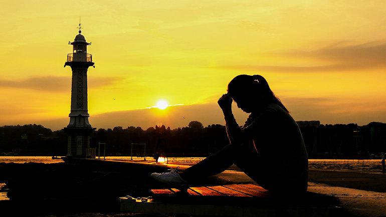 Naplementében imádkozó nő